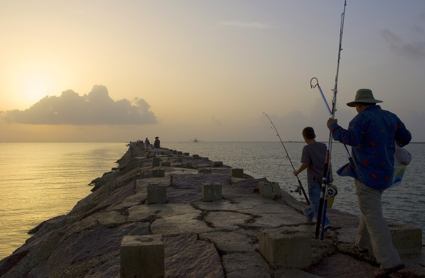 Father and son fishing at sunrise on jetty at South Padre.