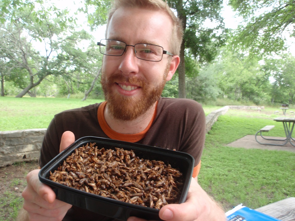 Robert Nathan Allen, founder of Little Herds, with a container of roasted crickets at McKinney Falls State Park, photo by Cecilia Nasti.