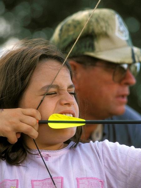 Teaching children archery skills.