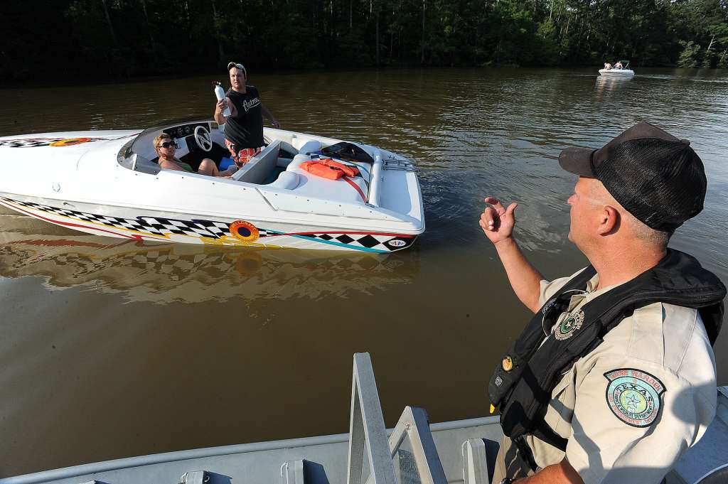Mike Boone, game warden for the TPWD, checks boaters along the Neches River for violations. Image: Beaumont Enterprise]