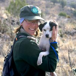Park ranger with shelter dog on David Mountains hike.